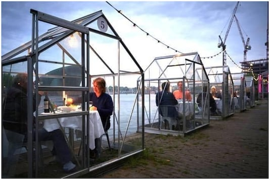 A Dutch fine dining restaurant has decided to install glass booths to allow diners to eat out while social distancing. | Image credit: Twitter