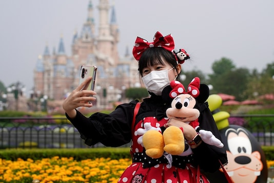 A visitor dressed as a Disney character takes a selfie while wearing a protective face mask at Shanghai Disney Resort as the Shanghai Disneyland theme park reopens following a shutdown due to the coronavirus disease (COVID-19) outbreak, in Shanghai, China May 11, 2020. (Photo/Reuters)