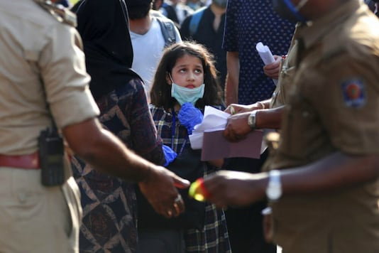 A stranded Kashmiri girl anxiously looks at officials checking documents as she waits with elders to board a bus to a special train home during a lockdown to curb the spread of new coronavirus, in Bangalore. (Image: AP)
