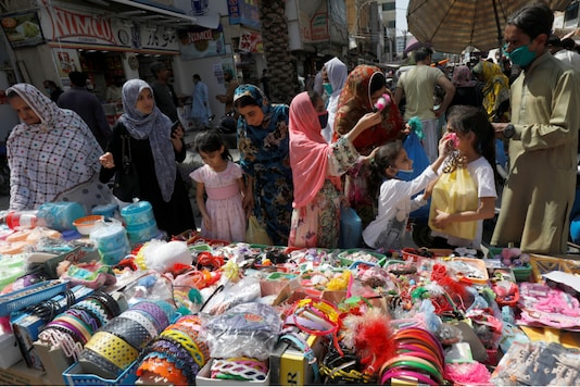 Women and children shop from a stall in a market, after Pakistan started easing the lockdown as the coronavirus disease (COVID-19) continues, in Karachi, Pakistan May 11, 2020. REUTERS/Akhtar Soomro