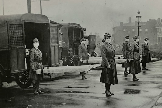 Mask-wearing women hold stretchers near ambulances during the Spanish Flu pandemic in US in October 1918. (Library of Congress/Handout via Reuters)
