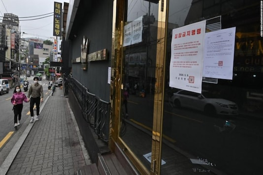 A couple wearing face masks walk past a night club, now closed following a visit by a confirmed Covid-19 coronavirus patient, in the popular nightlife district of Itaewon in Seoul on May 10, 2020.