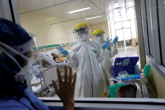 Health workers wearing protective suits gesture from the isolation room for the coronavirus disease (COVID-19) patients after taking swab samples, at the emergency unit at Persahabatan Hospital in Jakarta, Indonesia. (Reuters)