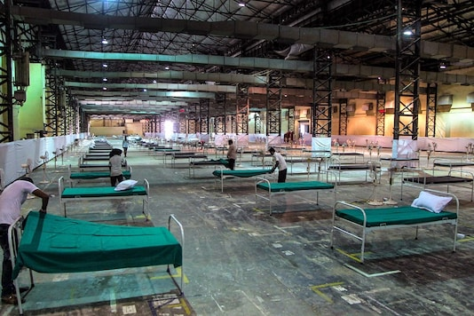 Workers prepare an quarantine center (isolation centre) for non-critical COVID-19 patients at the Bombay Exhibition Centre (NESCO Ground) in Mumbai. (PTI Photo)