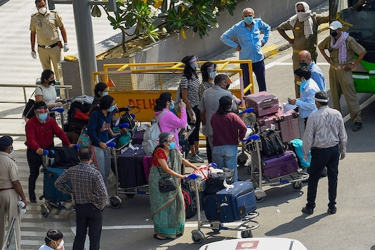 Indian nationals from Singapore prepare to leave in buses after they were brought by a special Air India flight at IGI Airport in New Delhi. (PTI Photo)