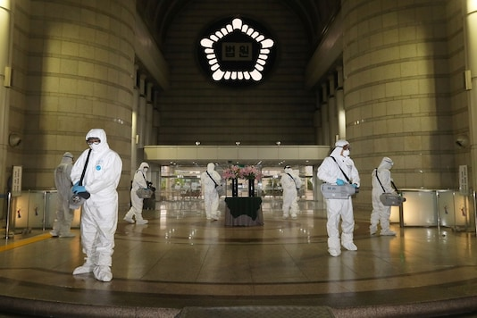 FILE PHOTO:  Quarantine workers spray disinfectant at the Seoul district court building, following the coronavirus disease (COVID-19) outbreak, in Seoul, South Korea.  Yonhap/via REUTERS/File photo