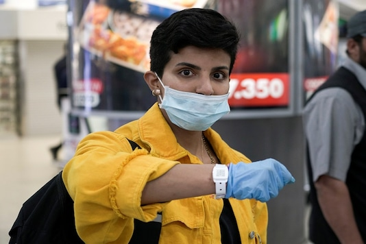 A Kuwaiti woman wearing a protective face mask poses as she shows her quarantine tracking bracelet upon her arrival from Amman to Kuwait Airport, following the outbreak of the coronavirus disease (COVID-19), in Kuwait City. (Reuters)