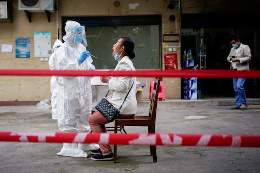 File photo: A medical worker in protective suit conducts nucleic acid testings for residents at a residential compound in Wuhan, the Chinese city hit hardest by the coronavirus disease (COVID-19) outbreak, Hubei province, China. (Image: Reuters)