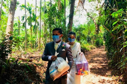 In this April 27, 2020, photo, Darshana Kumara Wijenarayana and his bride Pawani Rasanga walk with packets of food to distribute in the small town of Malimbada, about 160 kilometers (99 miles) south of the capital Colombo. (Darshana Kumara Wijenarayana via AP)