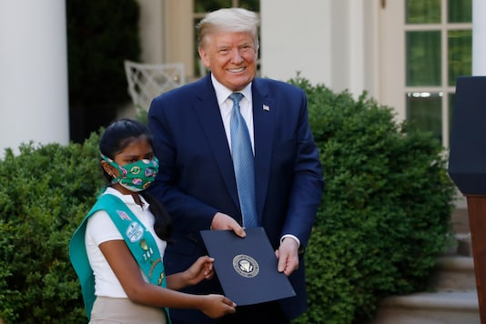 President Donald Trump poses for a photo with Girl Scout Troop 744 member Sravya Annappareddy during a presidential recognition ceremony in the Rose Garden of the White House, Friday, May 15, 2020, in Washington. (AP Photo/Alex Brandon)