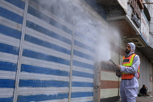 A rescue worker sprays disinfectant on closed shops at a market, after Pakistan started easing the coronavirus disease (COVID-19) lockdown, in Peshawar. (Reuters)