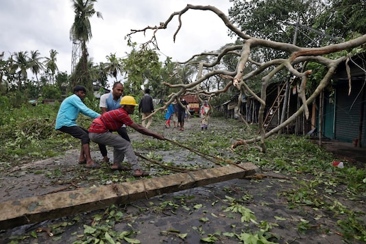 File photo: Men remove a fallen electricity pole from a road after cyclone Amphan made its landfall in South 24 Parganas district on West Bengal on Thursday. (Reuters)
