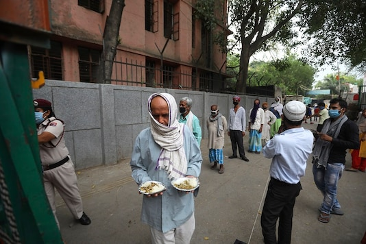 An impoverished man walks after receiving food prepared by the Bangla Sahib Gurdwara kitchen as others wait in a queue in New Delhi. (AP Photo)