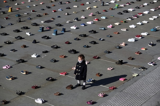 A child wearing a face mask stands surrounded by shoes in London, Britain. (Reuters)