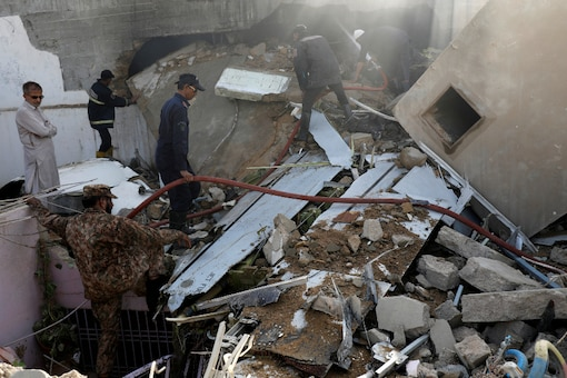 File Photo: Soldiers look at the debris of a plane after crashed in a residential area near an airport in Karachi, Pakistan. (Reuters)