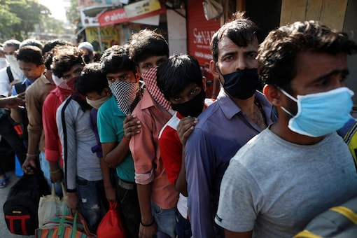 Migrants wearing protective face masks stand in a queue as they wait for transportation in Mumbai. (REUTERS)