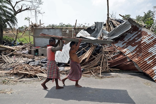 Residents carry tin sheets salvaged from the rubble of a damaged house in the aftermath of Cyclone Amphan, in South 24 Parganas district in West Bengal, India, May 22, 2020. REUTERS/Rupak De Chowdhuri