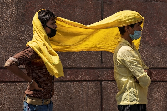 Migrant workers cover themselves with a scarf to protect from the heat in New Delhi. (Reuters)