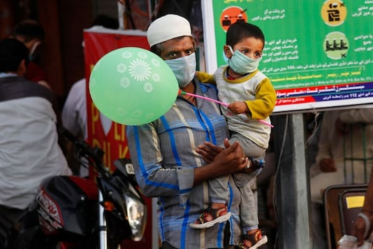 An man carries a child as they return after shopping for Eid al-Fitr, at the old quarters of New Delhi, India, Sunday, May 24, 2020.  (AP Photo/Manish Swarup)
