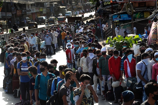 File photo: Migrant workers line up to board buses for their onward journey by train to their home states, at Dharavi, one of Asia's largest slums, in Mumbai, on May 22, 2020. (AP Photo/Rafiq Maqbool)