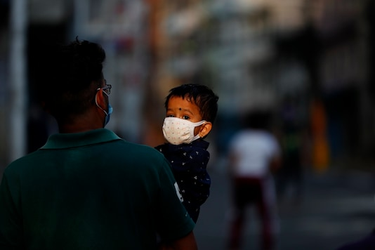 A Nepalese man carries his child as they return from a market during lockdown in Kathmandu, Nepal, Sunday, May 17, 2020. (AP Photo/Niranjan Shrestha)