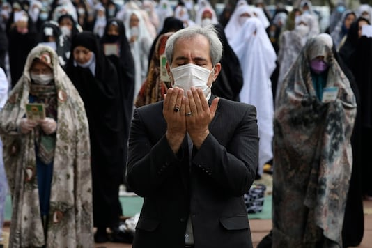 Worshippers wearing protective face masks offer Eid al-Fitr prayers outside a mosque to help prevent the spread of the coronavirus, in Tehran, Iran, Sunday, May 24, 2020. (AP Photo/Vahid Salemi)