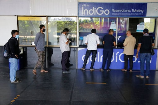 Passengers stand in queue at an airline ticket counter as domestic flights resume operations after nearly two-month lockdown amid the COVID-19 pandemic in Ahmedabad. (Image: AP)