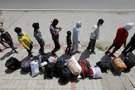 Migrant workers and their families wait to get on a bus to reach a railway station to board a train to their home state of Uttar Pradesh, during an extended lockdown to slow the spreading of the coronavirus disease (COVID-19), in New Delhi, India, May 26, 2020. Photo: (REUTERS/Adnan Abidi)