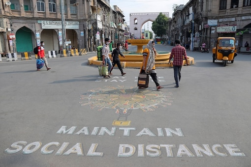 File photo: People walk past an art work displayed on a road urging people to stay home and maintain social distance during lockdown to prevent the spread of coronavirus in Hyderabad. (AP Photo)