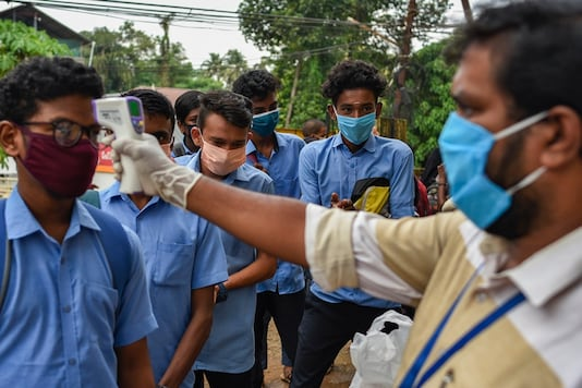 School children wearing masks get their hands sanitized and temperatures checked as they arrive to appear for state board examination during the coronavirus pandemic in Kochi, Kerala state, India, (AP Photo/R S Iyer)
