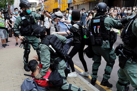FILE PHOTO: Anti-government demonstrators scuffle with riot police during a lunch time protest as a second reading of a controversial national anthem law takes place in Hong Kong, China May 27, 2020. REUTERS