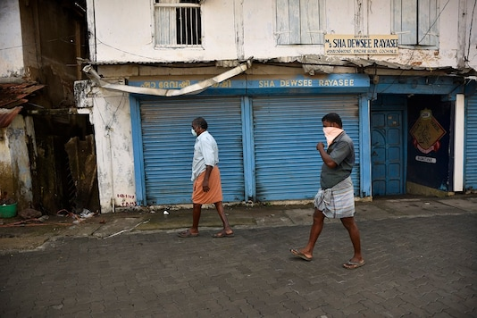 Residents wearing masks as a precaution against the coronavirus walk at a wholesale market in Kochi, Kerala state, India, Wednesday, May 20, 2020. (AP Photo/R S Iyer)