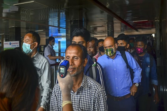 A medical official measures the temperature of a passenger using an infrared thermometer, following the outbreak of coronavirus. (PTI Photo)
