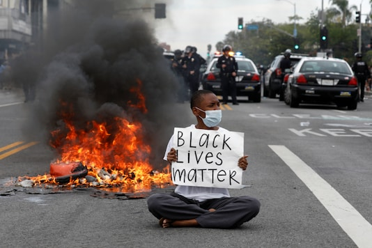 A demonstrator holds a placard during a protest against the death in Minneapolis police custody of George Floyd, in Los Angeles, California, U.S., May 30, 2020. REUTERS/Patrick T. Fallon