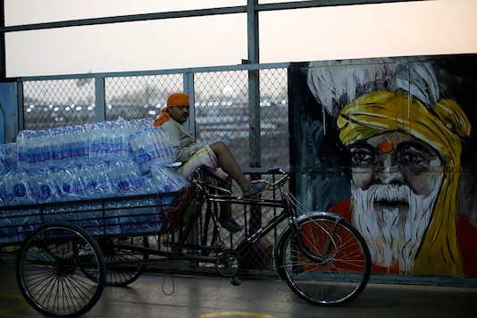 A man sits on a cart loaded with drinking water bottles to distribute to migrant workers arriving on a train from Maharashtra state, in Allahabad on Sunday. (AP)
