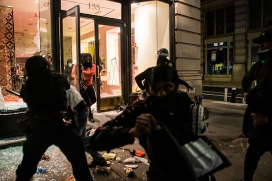 People take luxury products from a smashed storefront during a protest against the death in Minneapolis police custody of George Floyd, in the Manhattan borough of New York City, US., May 31, 2020. Picture taken May 31, 2020. (REUTERS/Jeenah Moon)