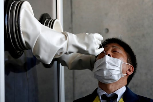FILE PHOTO: A medical worker conducts a simulation for a walk-in style polymerase chain reaction (PCR) test for the coronavirus disease (COVID-19), at a makeshift facility in Yokosuka, south of Tokyo, JapanREUTERS/Issei Kato/File Photo