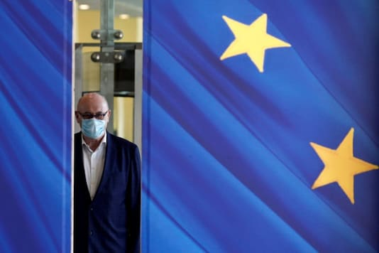 FILE PHOTO: A man wearing a face mask walks past the European Commission headquarters as the spread of coronavirus disease (COVID-19) continues in Brussels, Belgium May 14, 2020. REUTERS/Johanna Geron/File Photo