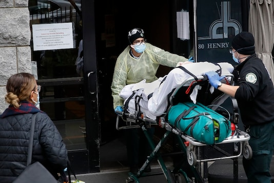 A patient is wheeled into Cobble Hill Health Center by emergency medical workers in the Brooklyn borough of New York. (AP Photo)