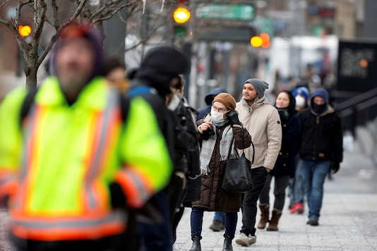 A woman adjusts her mask while she waits in line as the city's public health unit holds a walk-in clinic testing for coronavirus disease (COVID-19) in Montreal, Quebec, Canada.  (Reuters/Christinne Muschi/Files)