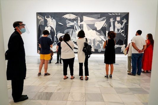 Visitors look at Pablo Picasso's painting 'Guernica' as the Reina Sofia museum reopens to the public, amid the coronavirus disease (COVID-19) outbreak, in Madrid, Spain, June 6, 2020. REUTERS/Juan Medina