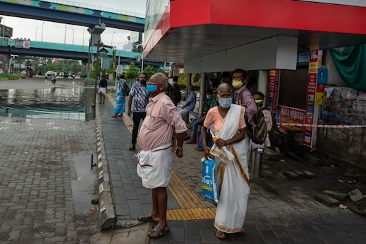 People wearing face masks to protect from the new coronavirus as they wait for bus transport in Kochi, Kerala. (AP)