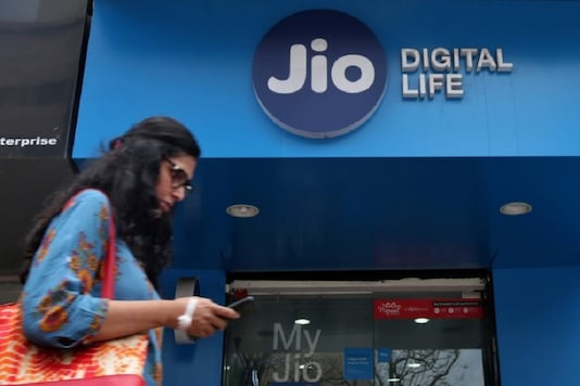 A woman checks her mobile phone as she walks past a mobile store of Reliance Industries' Jio telecoms unit, in Mumbai. (Reuters)