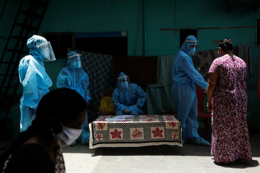 A woman wearing a mask crosses a healthcare camp set up in Mumbai's Dharavi. (Reuters)