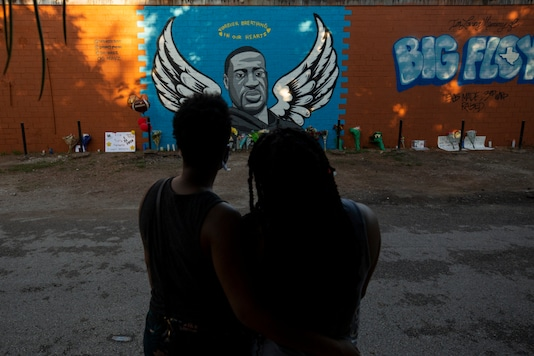 LaQuincia Pittman, left, and her wife Kaysi Higgins look at the George Floyd mural in Third Ward on Wednesday, June 3, 2020, in Houston. in Houston. Floyd died after being restrained by Minneapolis police officers on May 25. (Godofredo A. Vásquez/Houston Chronicle via AP)
