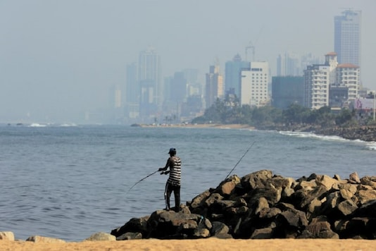 FILE PHOTO: A man fishes near a deserted beach as the Colombo financial city is seen behind him in Sri Lanka. REUTERS/Dinuka Liyanawatte/File Photo