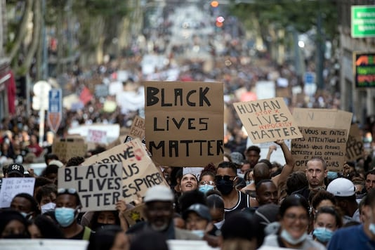 "In this representative image, a protester looks up at a sign that reads ""Black Lives Matter"". (AP)"