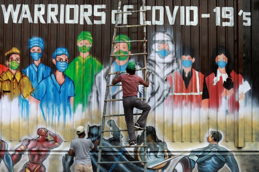 A man gets off a ladder after completing a mural honouring Covid-19 warriors in Delhi. (Reuters)