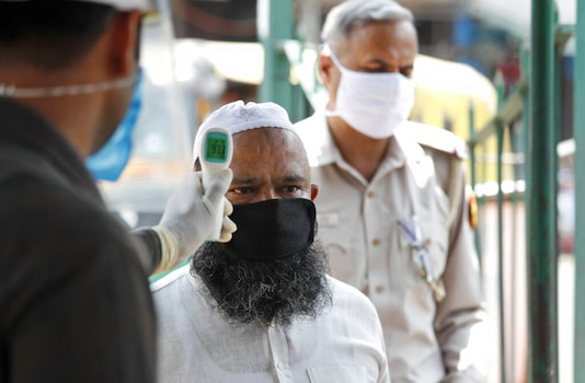 For Representation. A security person checks the temperature of a man who arrives to offer prayers after Jama Mosque opened after lockdown in New Delhi. (Image: AP)