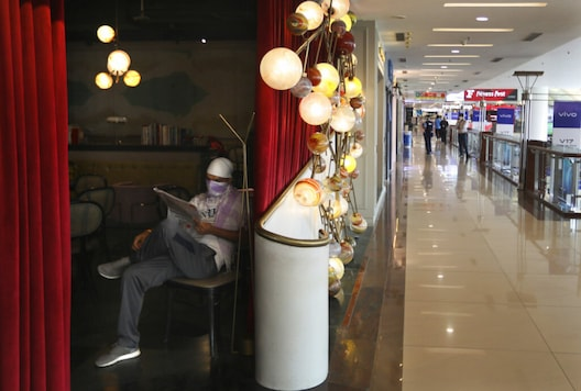 An employee of a restaurant reads a newspaper at a shopping mall that reopened in New Delhi. (Image: AP)